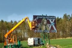 Montaż tablicy reklamowej w terenie z wykorzystaniem podnośnika koszowego